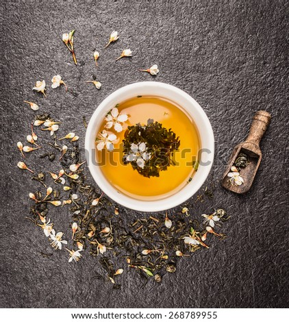 Cup of Jasmine tea, old wooden scoop and fresh flowers on dark stone background, top view - stock photo