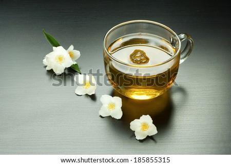 cup of jasmine tea with jasmine flowers on black wooden table - stock photo