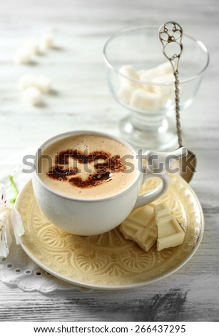 Cup of latte coffee art on wooden table, on light background - stock photo