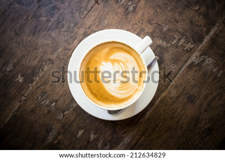 Cup of latte coffee on wood - stock photo