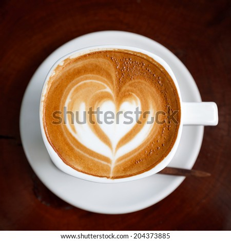 Cup of latte coffee on wooden - stock photo