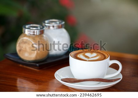 Cup of latte coffee on wooden table  - stock photo
