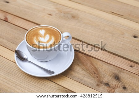 cup of latte on a wooden table from the pallet - stock photo