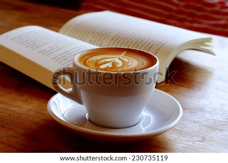 cup of latte or cappuccino coffee with a book in coffee shop with vintage retro filter effect - stock photo