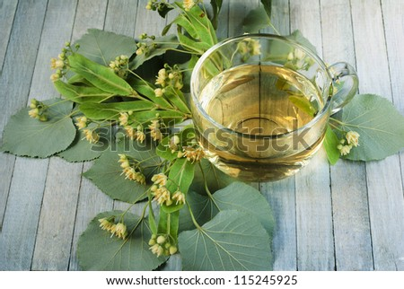 cup of lime tree tea and linden flowers, bright wooden table