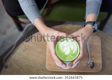Cup of Matcha Green Tea in woman hand - stock photo
