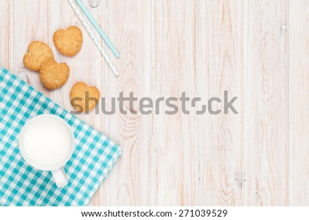 Cup of milk and heart shaped cookies on white wooden table with copy space - stock photo
