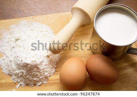 cup of milk, flour and two eggs - stock photo