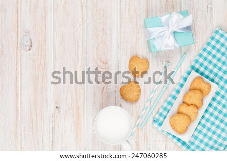 Cup of milk, heart shaped cookies and gift box on white wooden table with copy space - stock photo