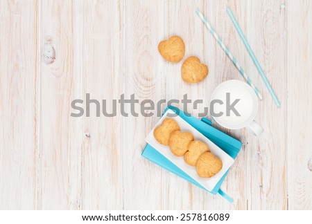Cup of milk, heart shaped cookies and notepad on white wooden table with copy space - stock photo