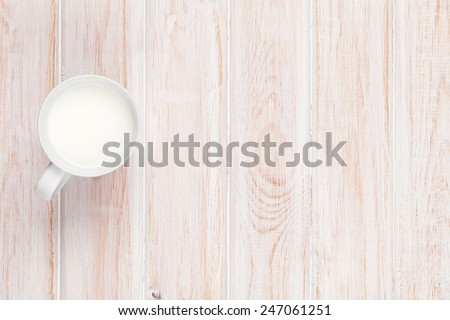 Cup of milk on white wooden table. View from above with copy space - stock photo