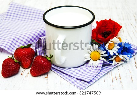 Cup of milk, strawberries and wildflowers on a old wooden background - stock photo