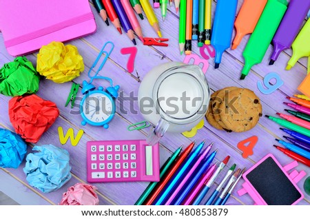 cup of milk with cookies and supplies on purple wooden table