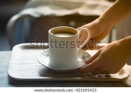 Cup of morning cofee in girls hands on wooden table