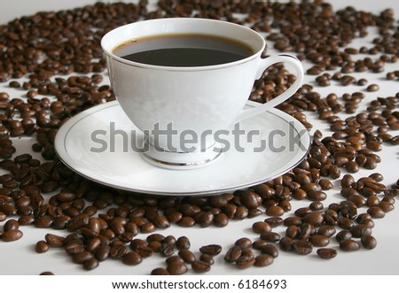 cup of morning coffee,and coffee beans - stock photo