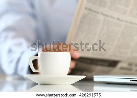 Cup of morning coffee on worktable with business analyst hold in hands and read newspaper on background. Price quotation on the exchange, relaxing at workplace, or football match result concept