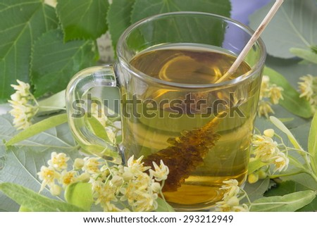 Cup of natural lime tea with sugar stick, lemon and lime flowers - stock photo