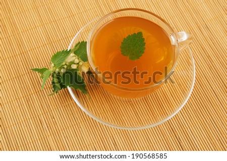 Cup of nettle tea on bamboo mat - stock photo