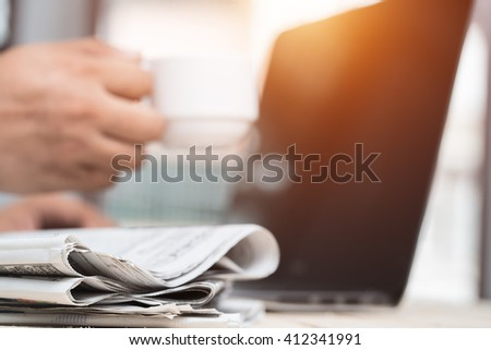 Cup of  Newspaper on the desk businessman. - stock photo