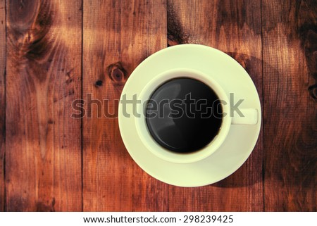 Cup of ?offee on a wooden table.