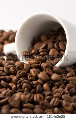 Cup of roasted brown coffee beans on white background