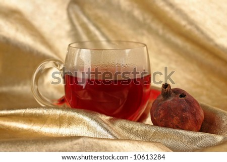 Cup of roibos fruit tea with dry pomegranateon textile gold background