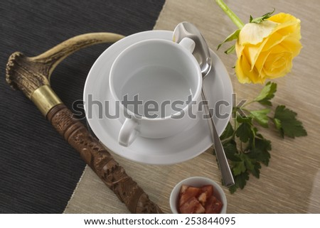 cup of soup on the dark background prepared for garnish with yellow rose - stock photo