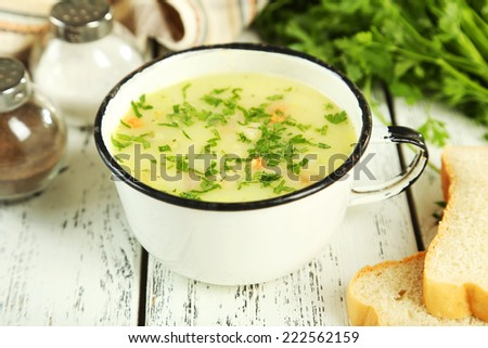 Cup of soup on white wooden background - stock photo
