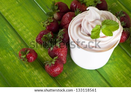 Cup of strawberry frozen yogurt or soft serve ice cream with fresh fruit. - stock photo