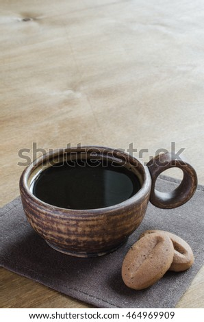 Cup of tasty coffee with cookies on wooden table. Coffee break, relax time. Selective focus.