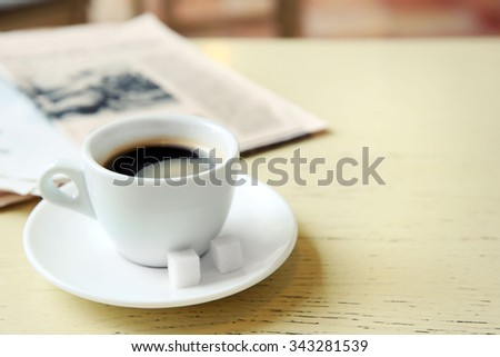 Cup of tasty coffee with newspaper and sugar on table