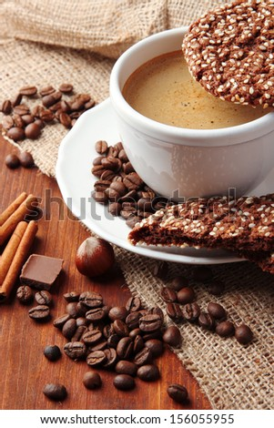 Cup of tasty coffee with tasty cookies, on wooden background - stock photo