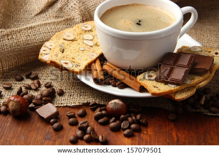 Cup of tasty coffee with tasty Italian biscuits, on wooden background - stock photo
