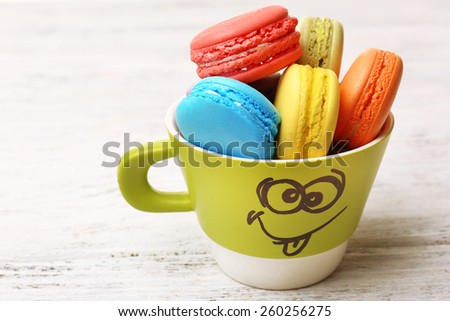 Cup of tasty colorful macaroons on color wooden background - stock photo