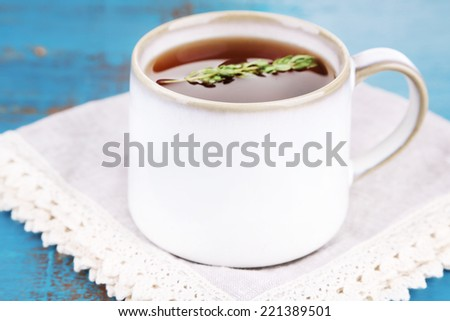 Cup of tasty herbal tea with thyme on blue wooden table - stock photo