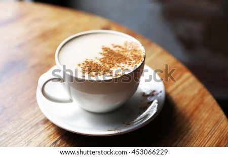 Cup of tasty latte is standing on the wooden textured table with the brick wall background.  Latte is in the white big cup.