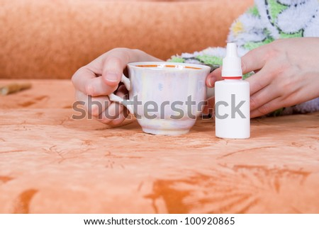 cup of tea and a nasal spray against the couch - stock photo