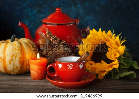 Cup of tea and Autumn thanksgiving decor with candle, sunflower and pumpkin - stock photo