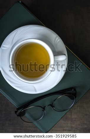 Cup of tea and book on wooden table, from above - stock photo