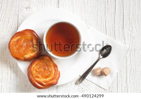 Cup of tea and buns with apricot jam on white wooden table, top view