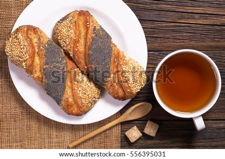 Cup of tea and buns with sesame and poppy seeds in plate on wooden table, top view