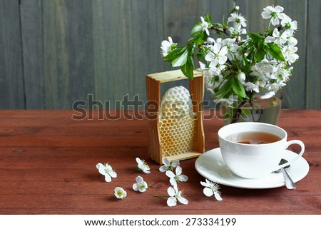 Cup of tea and cherry with  honeycomb on a wooden background - stock photo