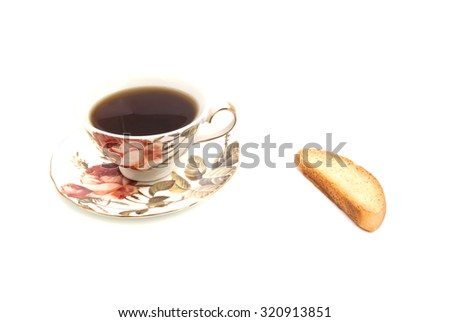 cup of tea and cracker on white - stock photo