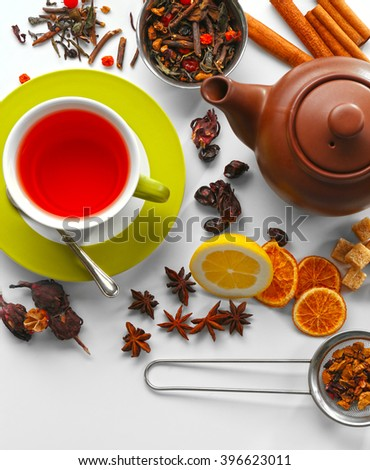 Cup of tea and delicious ingredients on table - stock photo