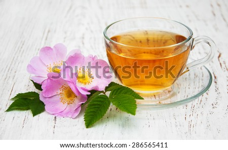 Cup of tea and dog rose on a old wooden background - stock photo