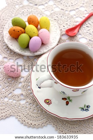 cup of tea and easter eggs on beautiful napkin - stock photo