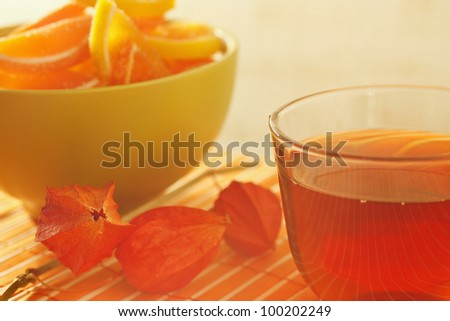 Cup of tea and fruit jelly with physalis on a bamboo table cloth still life - stock photo