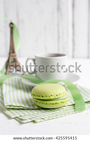 Cup of tea and green French macaroons on a white wooden background. Selective focus.