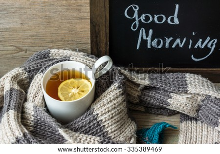 Cup of tea and knited scarf Good morning note on a chalkboard - stock photo