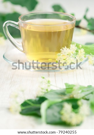 Cup of tea and linden flowers on wooden background - stock photo